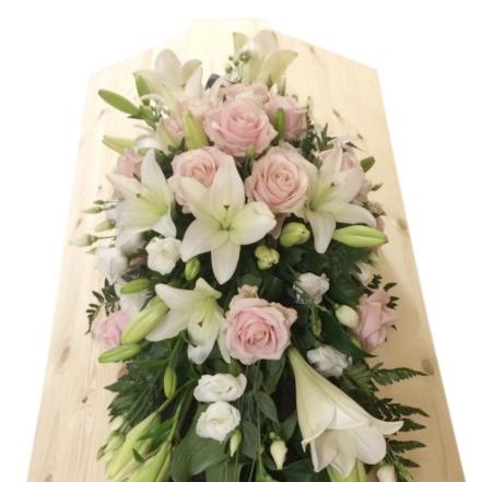 Begravningsblommor på ljus begravningskista som innehåller ljusrosa rosor, liljor och vit prärieklocka.