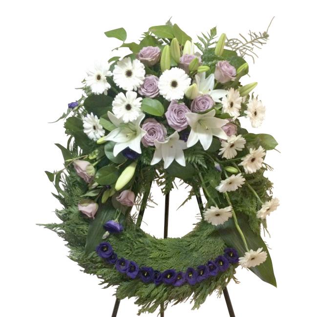 Grön begravningskrans gjord på blad med vita och ljus lila blommor på toppen av kransen. Längst ner på kransen finns en rad med små mörk lila blommor. Kransen är i mitten av en vit bakgrund och är en begravningsblomma.