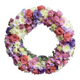 Begravningskrans i oasis stomme fylld med blommor i lila och cerise vitt. Blommorna fyller hela kransen. Kransen ligger i mitten av en vit bakgrund. Kransen är en typ av begravningsblomma,