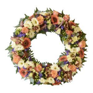 Begravningskrans med blommor i höstens färger i prärieklockor. orkidéer mm. Blommorna fyller hela kransen. Kransen är i mitten av en vit bakgrund och är en begravningsblomma.