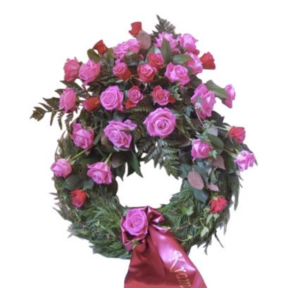 Grön begravningskrans med cerise samt mörk cerise rosor, längst ner på kransen finns ett band med texten ''Kram''. Kransen är placerad i mitten av en vit bakgrund och är en begravningsblomma.