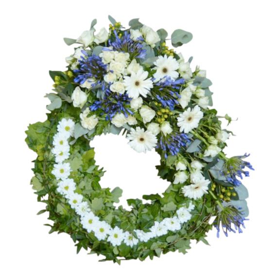 Grön stomme begravningskrans med lila och vita inslag, kransen är placerad i mitten av en vit bakgrund och är en typ av begravningsblomma.