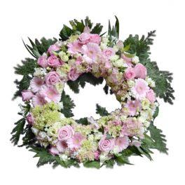 Begravningskrans med osis stommens.Kransens blommor är i gul,rosa samt vit. Under kransen finns det blad. Kransen är en begravningsblomma och är i mitten av en vit bakgrund.