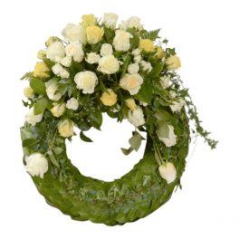 Grön begravningskrans med bladad stomme. Kransen har rosor i blandade gula och vita toner högst upp på kransen. Kransen är en begravningsblomma placerad i mitten av en vit bakgrund.