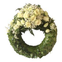 Grön begravningskrans med vita rosor, brudslöja samt prärieklocka. Blommorna är på översta delen av kransen.Kransen är i mitten av en vit bakgrund, och är en begravningsblomma.