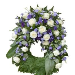 Lavendel begravningskrans med vita rosor och lila prärieklockor. Blommorna är runt hela kransen förutom nedersta delen av kransen. Kransen är i mitten av en vit bakgrund och är en begravningsblomma.