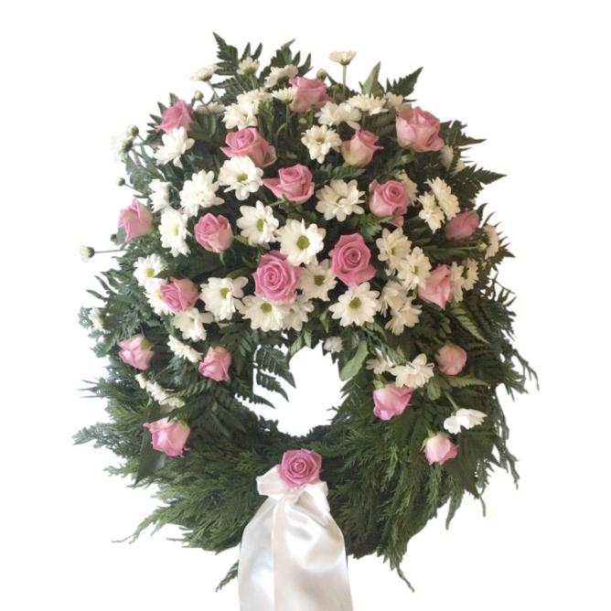 Grön begravningskrans med vit kryss och små rosa rosor.I mitten längst ner på kransen finns ett band som hänger ner.Kransen är en begravningsblomma och är i mitten av en vit bakgrund.