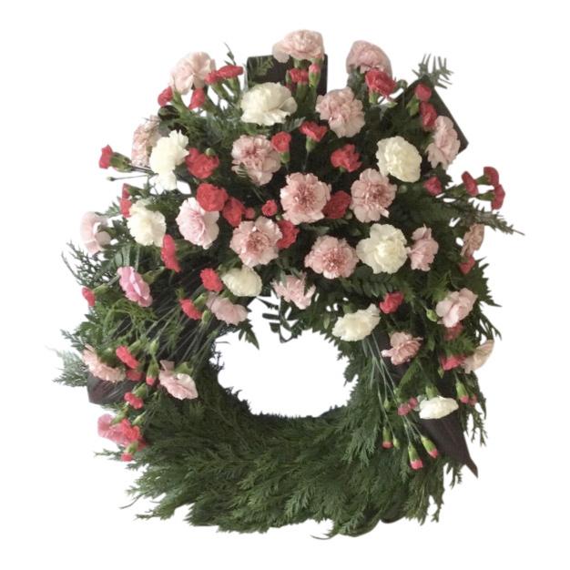Begravningskrans gjord av blad med nejlikor i cerise rosa samt vitt. Kransen är en begravningsblomma placerad i mitten av en vit bakgrund. Blommorna är runt hela kransen förutom längst ner.