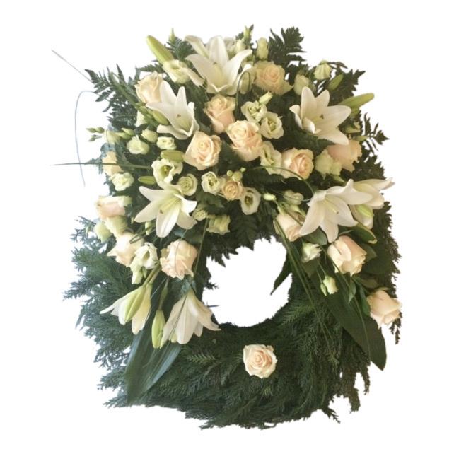 Begravningskrans gjord av blad med champagnerosor,vita liljor och pärireklockor. Blommorna är runt hela kransen förutom längst ner.Kransen är en begravningsblomma och är i mitten av en vit bakgrund.