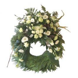 Grön begravningskrans med vita rosor, ornitugalum,prärieklocka samt skogsmaterial. Blommorna är runt hela kransen förutom längst ner. Kransen är en begravningsblomma och är i mitten av en vit bakgrund.