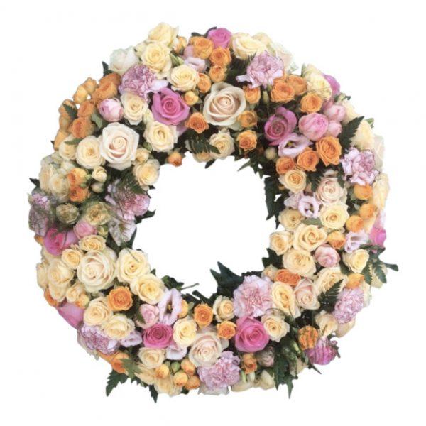 Oasias begravningskrans med rosor,nejlika och prärieklocka i varma pastel färger runt hela kransen. Kransen ligger i mitten av en vit bakgrund och är en begravningsblomma.