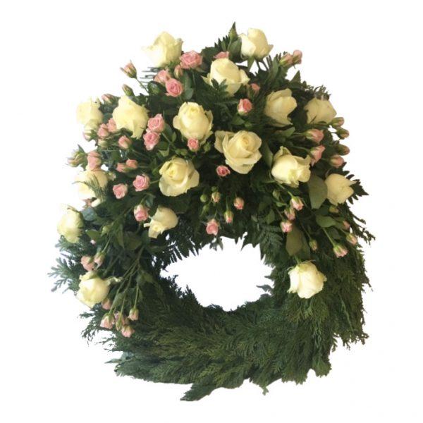 Begravningskrans med vita rosor och rosa kvistros på toppen. Kransen är en begravningsblomma och är i mitten av en vit bakgrund.