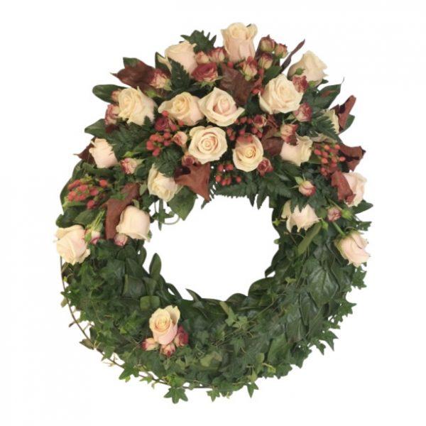 Höstig begravningskrans gjord av blad med champagnerosor,kvistrosor samt hyperikum.Blommorna är överst på kransen.Kransen är placerad i mitten av en vit bakgrund. Kransen är en begravningsblomma.