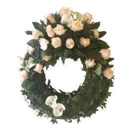 Grön begravningskrans gjord på blad med champagne rosor samt orkidéer. Kransen är en begravningsblomma och är i mitten av en vit bakgrund.