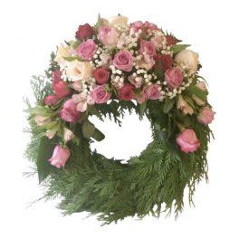 Liten begravningskrans med rosa rosor och brudslöja på toppen av kransen. Kransen är en typ av begravningsblomma och är placerad i mitten av en vit bakgrund.