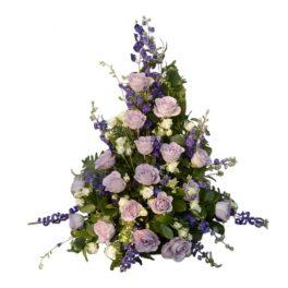 Sorgdekoration med begravningsblommor i lila samt vitt och med gröna blad.Buketten har riddarsporrar,rosor och vita kvistrosor. Buketten ligger i mitten av en vit bakgrund.