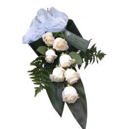 Begravningsblommor med bundna champagnefärgade rosor och mörkgröna blad som bildar en vacker och enkel sorgbukett i grönt och vitt.Buketten är i mitten av en vit bakgrund.
