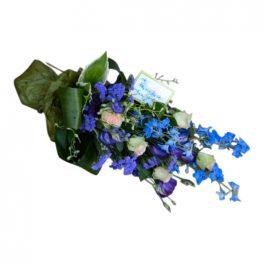 Begravningsblommor i färgerna blått och lila. Men även med lite vit ljusrosa rosor samt med mörkgröna blad.Blommorna bildar tillsammans en vacker bukett.