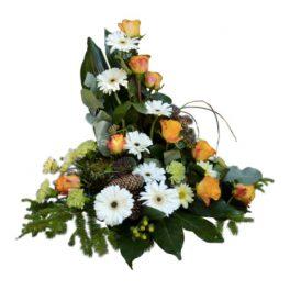 Sorgdekoration med begravningsblommor som har inspiration från skogen. Buketten är främst grön och består av blad men buketten har också gul orangea rosor och vita gerbera blommor samt skogsmaterial så som kottar.