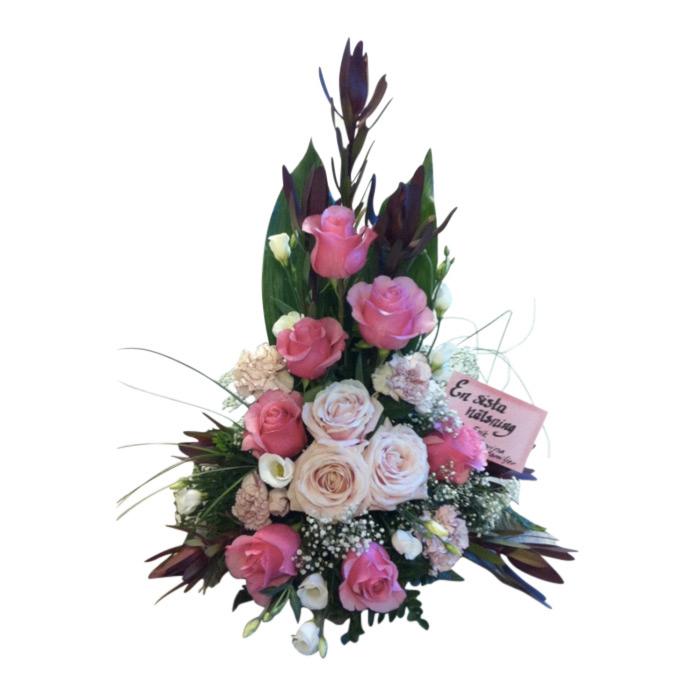 Sorgdekoration med begravningsblommor i rosa och grönt. Dekorationen har rosa rosor i olika toner. Åt vänster sida av den stående buketten finns en liten lapp med skrift.