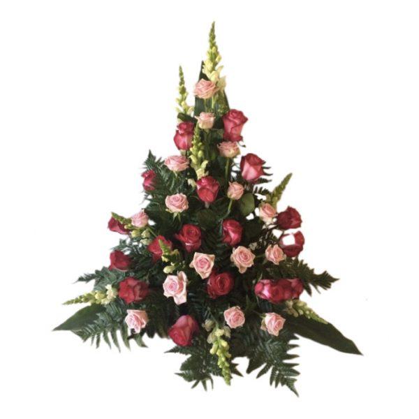 Sorgdekoration med begravningsblommor i rosa cerise rosor,lejongap och grönt.Blommorna bildar en vacker och stilren begravningsbukett.Buketten är mitten av en vit bakgrund.