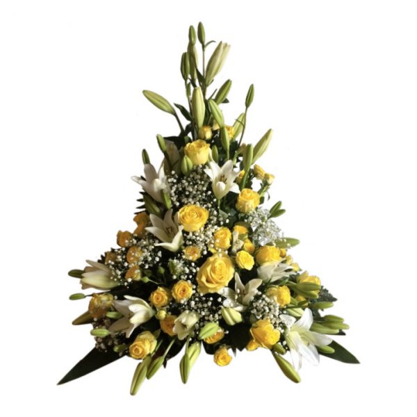 Gul och vit sorgdekoration med begravningsblommor som har vackra liljor,rosor,brudslöja samt blad. Buketten är ungefär formad som en triangel och är i mitten av en vit bakgrund.