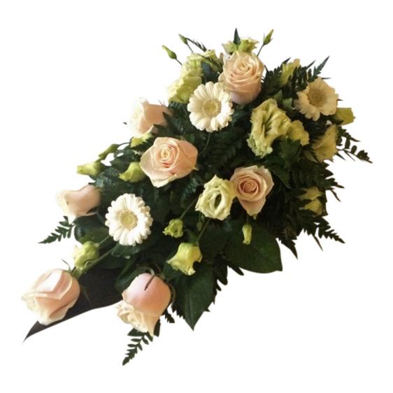 Liggande sorgdekoration med olika begravningsblommor så som champagnerosor,lime,prärieklockor och vit mini gerbera. Buketten har också vackra mörkgröna blad,och är i mitten av en vit bakgrund.