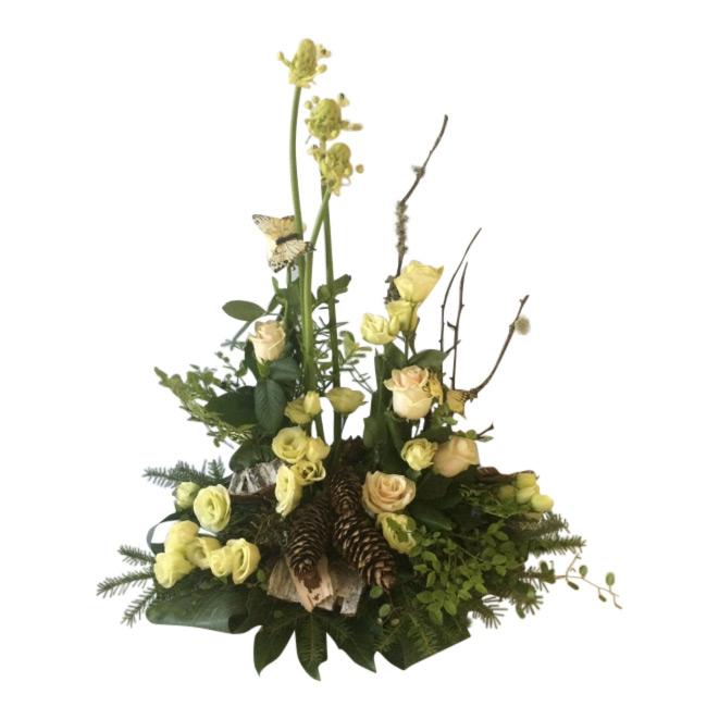 Fin sorgdekoration med begravningsblommor som innehåller champagnerosor,prärieklocka,ornitugalum,kottar, fjärilar och annat skogsmaterial. Buketten är vit och grön och är i mitten av en vit bakgrund.