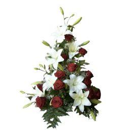 Sorgdekoration med begravningsblommor som har röda vackra rosor,vita fina liljor och gröna blad. Dekorationen är i mitten av en vit bakgrund.