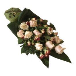 Begravningsblomma med fina kvistros och vackra champagne färgade rosor samt mörkgröna stora blad. Tillsammans bildar blommorna en vacker sorgbukett.