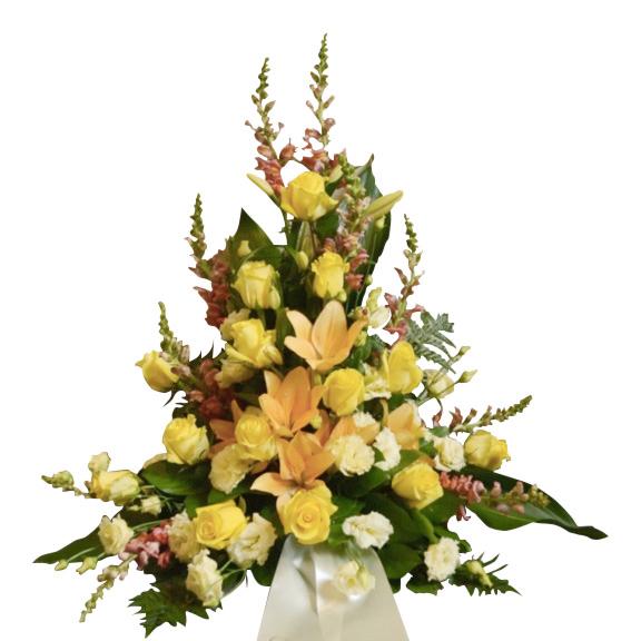 Sorgdekoration med begravningsblommor i främst gul tonade färger men också i crème och orange. Buketten har även ett vitt band som hänger ner samt gröna blad. Buketten är i mitten av en vit bakgrund.