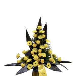 Sorgdekoration med begravningsblommor i AIK färger. Det vill säga i gult och svart. Buketten har gula rosor och minigerbera i mitten och svarta blad som sticker ut runt blommorna.Längst ner på buketten finns det ett band som hänger ner i AIK färger.