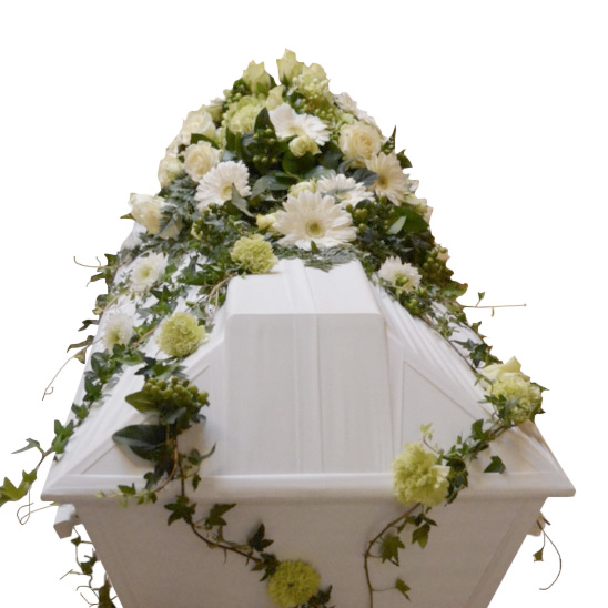 Begravningsblommor på vit begravningskista. Blommorna är i vitt och lime. De olika blommorna är rosor,nejlikor,gerbera samt murgröna.