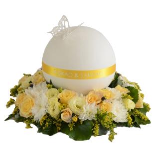 Gul Urndekoration med begravningsblommor i gult och vitt samt grönt. På urndekorationen ligger en rund urn i gult och vitt med en fjäril på ovansidan.