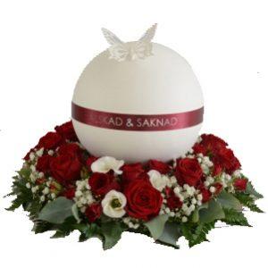 Vit rund urn med röda färger.Urnen har på ovansidan en vit fjäril.I mitten av urnen är en röd rand med texten ''Älskad och saknad''.Den ligger på en urndekoration med begravningsblommor i rött och vitt.