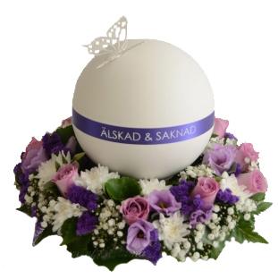 Rund vit urndekoration med lila färgschema, i mitten av urnen är en lila rand med texten ''Älskad och saknad''.På ovansidan finns en vit fjäril. Urnen ligger på flera begravningsblommor i lila,vit och rosa.