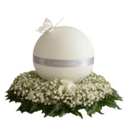 Stilren urndekoration med vita små begravningsblommor och gröna blad. En rund urn i grått och vitt är över urndekorationen. På ovansidan av urnen är en fjäril i vitt.