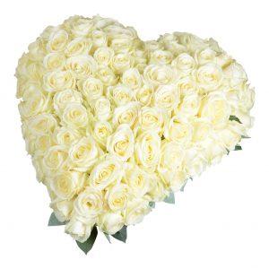 Elegant begravningsblomma bestående av ett stort hjärta fylld med vita stora rosor med små blad som sticker ut bakom hjärtat.Hjärtat är i mitten av en vit bakgrund.