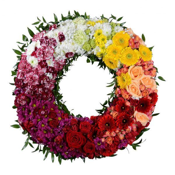 Begravningskrans med olika blommor i olika färger. Färgerna i kronologisk ordning är vit,gul,orange,röd,lila samt rosa. Kransen ligger i mitten av en vit bakgrund. Kransen är en typ av begravningsblomma.