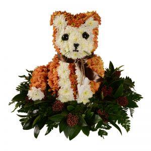 Personligt arrangemang begravningsblomma gjord av orangea och vita blommor som formar en katt. Katten sitter på flera blad. och har även ett brunt silkesband runt halsen.