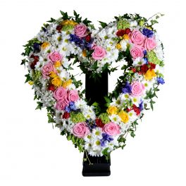 Begravningsblomma som består av ett öppet hjärta gjord av olika blommor i färger som speglar midsommaren så som vit,rosa,lila,gul och ljusgrön
