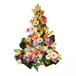 Ljuvlig sorgdekoration med begravningsblommor i liljor,gerbera,rosor och nejlikor i färgerna orange,rosa,vit och gul. Buketten är fristående och har gröna blad som går in i buketten.