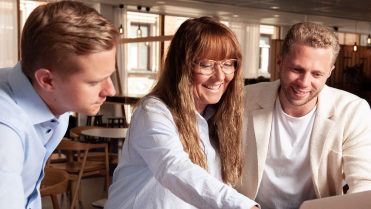 Tre medarbetare på Lavendla samlas runt en dator